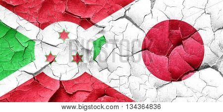 Burundi flag with Japan flag on a grunge cracked wall