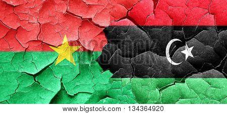 Burkina Faso flag with Libya flag on a grunge cracked wall