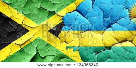Jamaica flag with rwanda flag on a grunge cracked wall