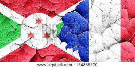 Burundi flag with France flag on a grunge cracked wall