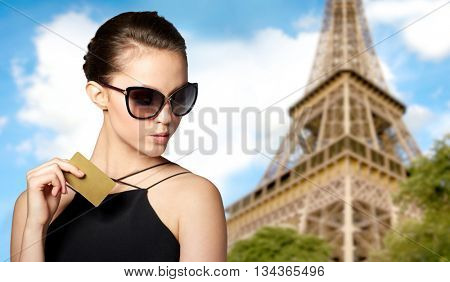 shopping tour, finances, travel, people and luxury concept - beautiful young woman in elegant black sunglasses with credit card over paris eiffel tower background