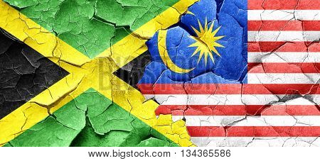 Jamaica flag with Malaysia flag on a grunge cracked wall