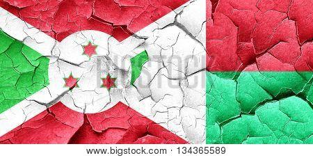 Burundi flag with Madagascar flag on a grunge cracked wall