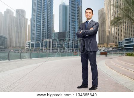 business, people and office concept - happy smiling businessman in dark grey suit over dubai city street background