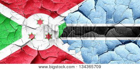 Burundi flag with Botswana flag on a grunge cracked wall
