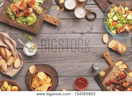 Outdoors Food Concept. On the wooden table different food with copy space grilled chicken legs buffalo wings bread salad potatoes potato chips and beer