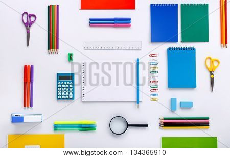 School supplies with a notebook with blank pages for your text on a white background. Flat lay top view