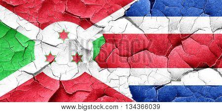Burundi flag with Costa Rica flag on a grunge cracked wall