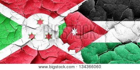 Burundi flag with Jordan flag on a grunge cracked wall