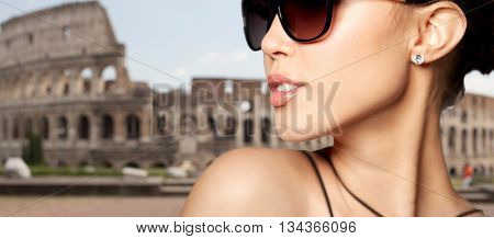 accessories, eyewear, fashion, people and luxury concept - close up of beautiful young woman in elegant black sunglasses over coliseum background