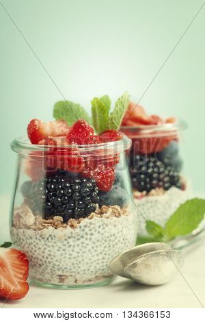 Chia seeds vanilla pudding and berries on blue background - Healthy food, Diet, Detox, Clean Eating or Vegetarian concept.