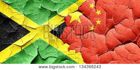 Jamaica flag with China flag on a grunge cracked wall