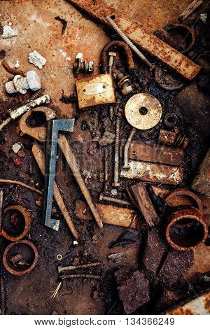 Various scattered metal junk rusty tools and other obsolete metal pieces