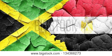 Jamaica flag with egypt flag on a grunge cracked wall