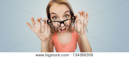 vision, education and people concept - happy smiling young woman or teenage girl eyeglasses over gray background