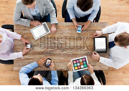 business, people, technology, media and team work concept - close up of creative team with smartphones and tablet pc computers sitting at table in office