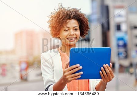 business, technology, communication and people concept - young smiling african american businesswoman with tablet pc computer in city