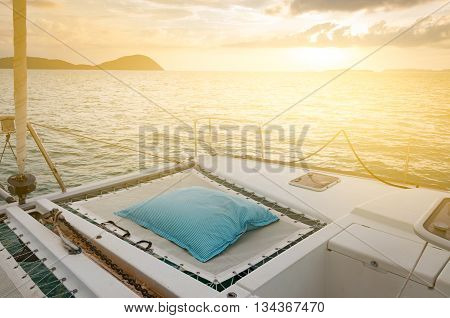 Luxury catamaran yacht deck. Blue and white stripes mattress for sunbathing during sunset in the evening with light effect