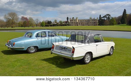 Saffron Walden, Essex, England - April 24, 2016: Two Classic cars in front of stately home, a Triumph Herald Convertible and a Jaguar.