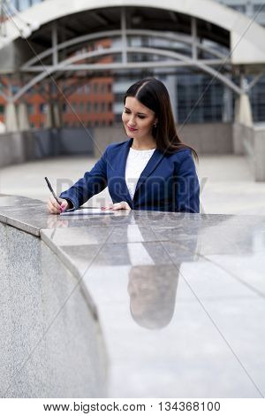 Young beautiful woman in a blue jacket signs the contract