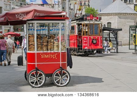 ISTANBUL TURKEY - JUNE 5 2016: The nostalgic tram pulling up beside a cart selling traditional Turkish simit bread at the Taksim Square end of the famous Istiklal Caddesi street. Tourists and locals enjoy the sunshine on a summer morning.