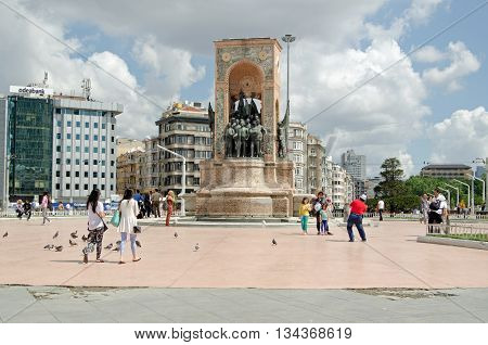 ISTANBUL TURKEY - JUNE 5 2016: Tourists and locals enjoying the sunshine and view at the Republic Monument in Taksim Square on a sunny summer morning.