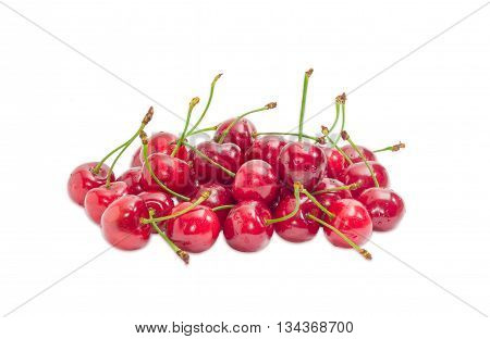 Pile of a ripe dark red sweet cherries with the stalks and water drops of on a light background