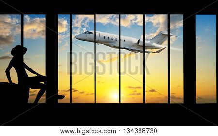 Young woman silhouette at Airport with suitcase. Private jet plane on background. Travel concept of air transportation
