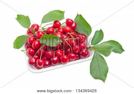 Ripe dark red sweet cherries with the stalks and several leaves of cherry in plastic tray on a light background