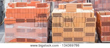 Wooden pallets of perforated yellow and red bricks with round holes on warehouse