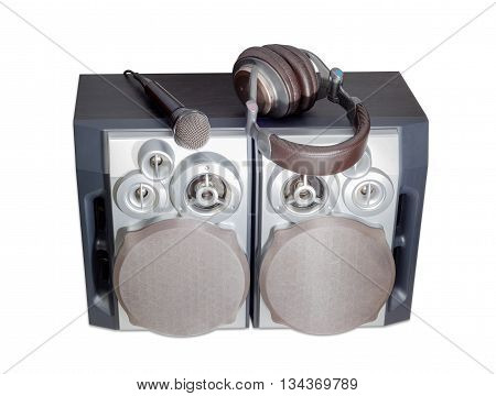 Black dynamic microphone and light brown full size headphones with soft headband on a four-way high fidelity loudspeaker system on a light background.