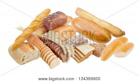 Several different types of bread and several wheat spikes on a light background
