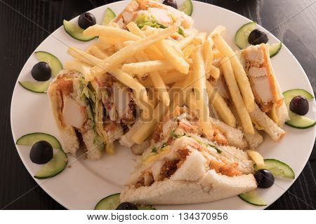 club sandwich and french fries in a white plate