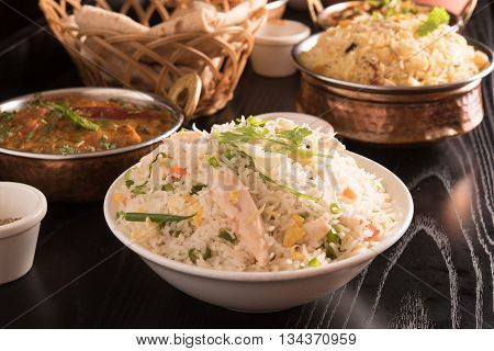 Fried rice in a white bowl with biryani and chapati