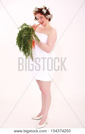 Young chubby woman wearing towel and curlers in your red hair eating a Karrotte while an entire covenant in your hand holds - Isolated on white.