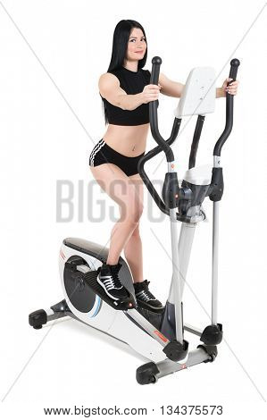 young woman doing exercises on elliptical cross trainer