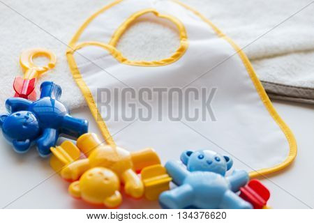 babyhood, childhood, accessory and object concept - close up of baby rattle and bib for newborn boy on towel