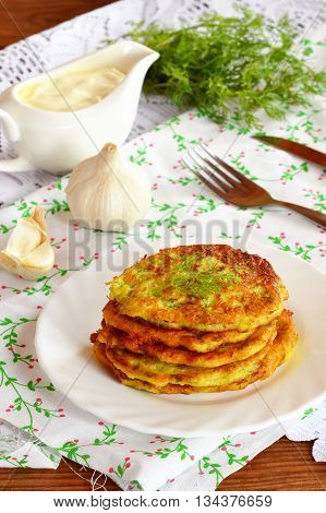 Zucchini fritters with garlic and dill on a plate. Green dill, garlic, fork, knife, gravy boat on a table. Easy and delicious meal idea for family. Close-up