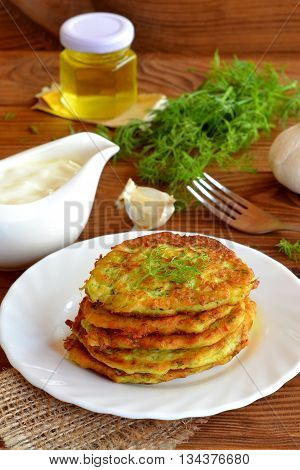 Vegetable fritters cooked with zucchini, garlic and dill. A stack of zucchini fritters on a plate. Bottle with vegetable oil, gravy with sour cream, garlic, green dill, fork on a wooden table. Macro