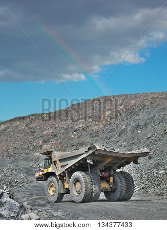 Heavy dump truck on the iron ore opencast with a rainbow in the sky