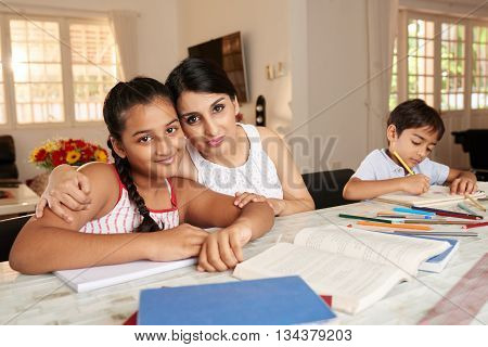 Cute girl doing homework with her mother