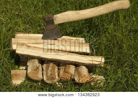 A stack of firewood and an ax on a green grass