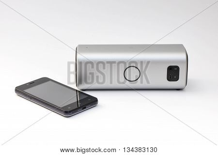 Wireless speaker connected to mobile phone - wireless mobile technology - On white background