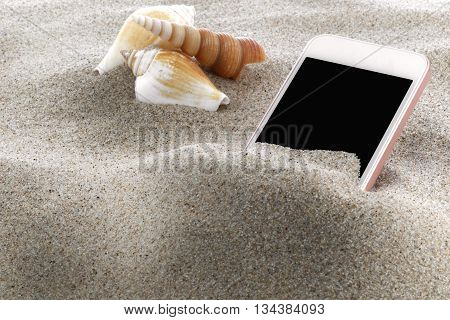 Mobile phone in sand on a beach