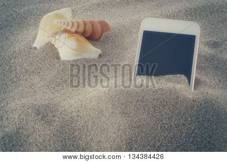 Mobile phone in sand on a beach vintage toned