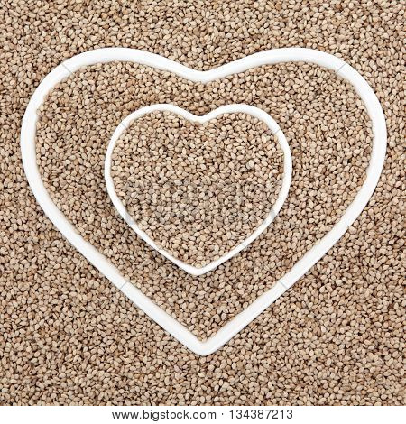 Sesame seed health food in heart shaped porcelain dishes forming an abstract background.