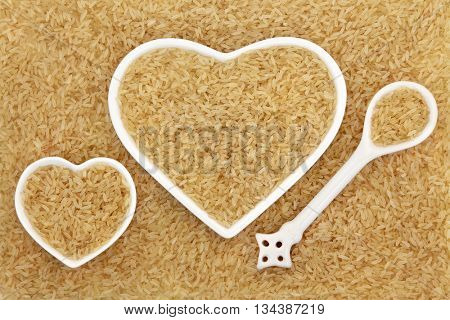 Long grain brown rice in heart shaped porcelain dishes and spoon forming an abstract background.