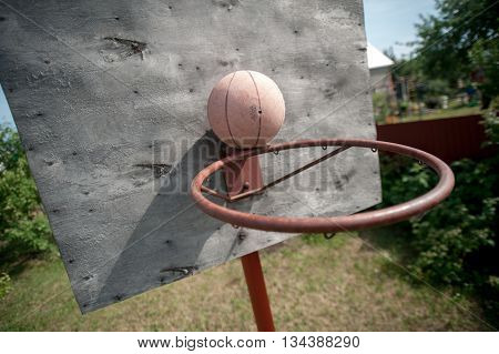 old basketball and the old basket on weathered wooden facade, outdoors, in the country