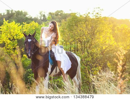 Young woman riding a horse at sunset