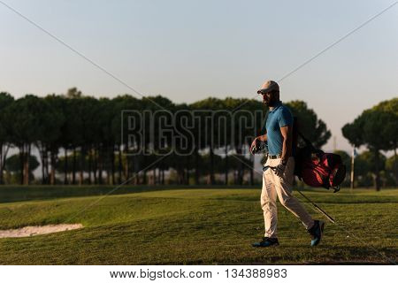 handsome middle eastern golfer  carrying  bag  and walking  to next hole at golf  course on beautiful sunset in background